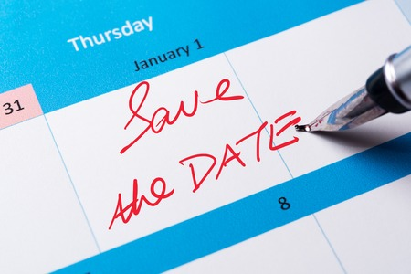 Save the date words written on calendar using pen Stock Photo