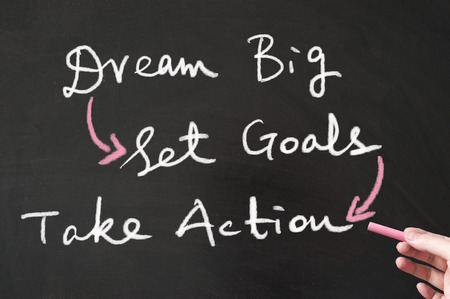 writing board: Dream big, set goals and take action words written on the blackboard using chalk