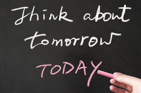 Think about tomorrow today words written on the blackboard using chalk