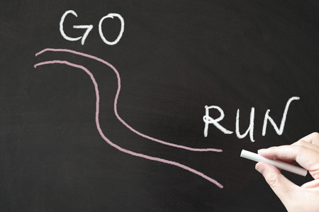 Go run words written on blackboard using chalk Stock Photo
