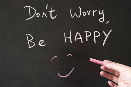 dont worry: Dont worry, be happy words written on the blackboard using chalk