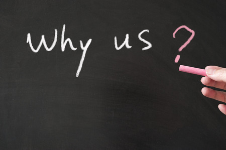why: Why us concept words written on the blackboard using chalk