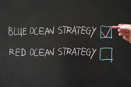 Blue or red ocean strategy words written on the blackboard using chalk Stock Photo