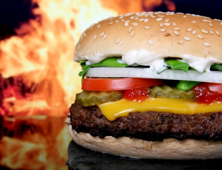 Silhouette of a cheese burger loaded with summer garden vegetables isolated on fire, macro photo