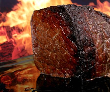 English roast meat by fire with flames, traditionally eaten with yorkshire pudding, macro, close up with copy space
