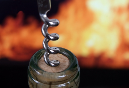 Wine bottle by orange flames with silver corkscrew, macro, close up Stock Photo