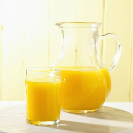Glass and Pitcher of Orange Juice Stock Photo