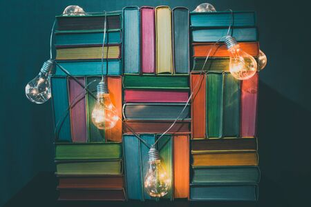 Colorful books with yellow light bulbs illumination on blue background