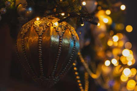 Closeup golden Christmas ball illuminated by yellow garland lights