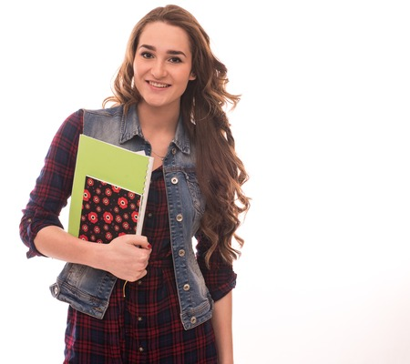Smiling young female student with books and bag against a white background.