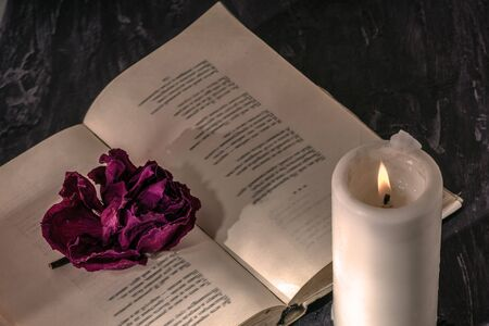 an open book with a candle. on the pages is a Bud of dried rose.