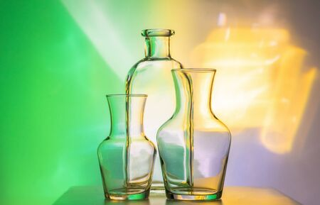 Glass transparent tableware - bottles of different sizes, three pieces on a beautiful multi-colored, yellow, and green, background. very beautiful still life.