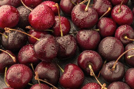 Cerca del montón de cerezas maduras con tallos. Gran colección de cerezas rojas frescas. Fondo de cerezas maduras.