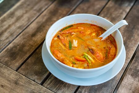 Tom Yam Kung, Thai cuisine. on a wooden table.