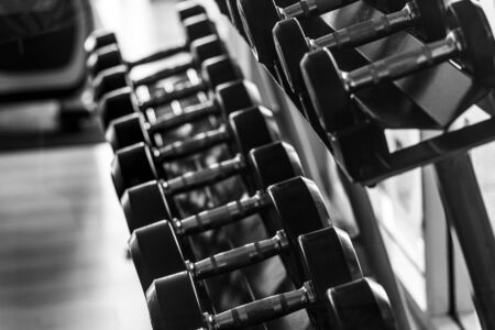 Black dumbbell set. Close up many metal dumbbells on rack in sport fitness center , Weight Training Equipment concept. vertical layout.