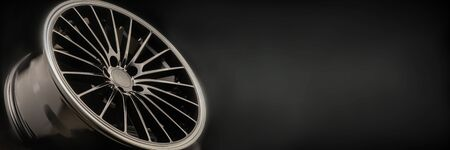 new Luxury Black alloy Wheel, sporty with thin spokes, copy cpace on black background.