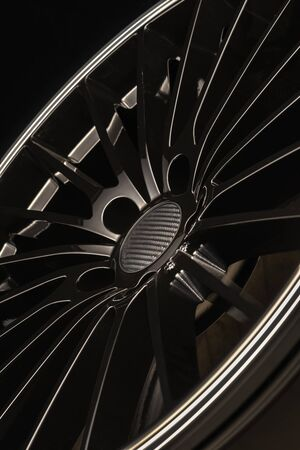 new Luxury Black alloy Wheel, sporty with thin spokes, close-up on black background, vertical layout.
