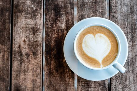 a mug of cappuccino coffee with a painted heart stands on a wooden textured table. top view, close-up. free empty space