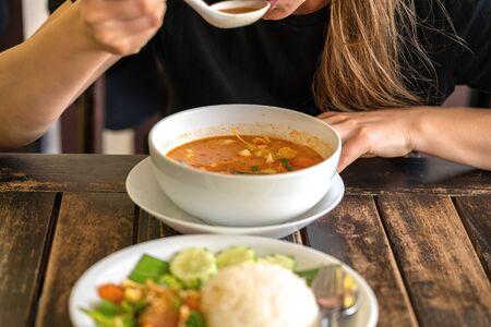 Girl eating Tom Yam Kung, Thai cuisine. close up Stock Photo