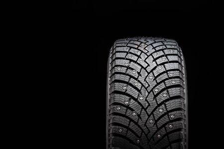 Neuer Winterreifen mit Spikes, Sicherheit und Premium-Qualität. schwarzer Hintergrund, Nahaufnahme