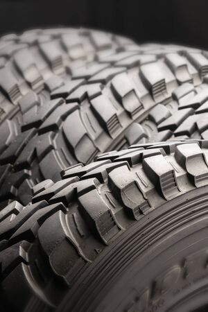 four off-road tires on black background. close up.