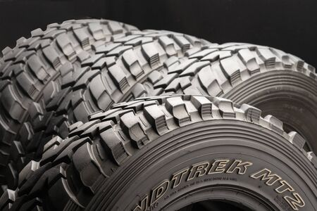 Krasnoyarsk, Russia 20 august 2019: four off-road tires on black background. close up. Editorial