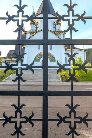 Orthodox Church domes, against the sky. Novo-Uspensky monastery in Krasnoyarsk, Russia. Clouds, a fragment of the building. view through the wrought iron grille.