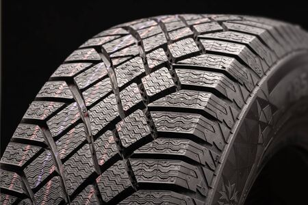 modern winter friction tyres  . safe driving. image wheel on a black background, rubber products, auto parts.