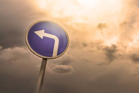 Turn left ahead sign, blue round roadside traffic signage, against the dramatic sky.