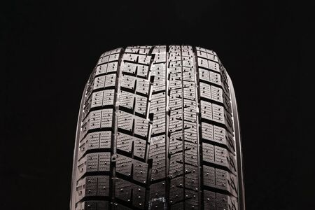 new non-directional asymmetric friction winter tire without spikes on a black background. rubber for ice water and snow. seasonal change of tires in autumn or winter. Фото со стока