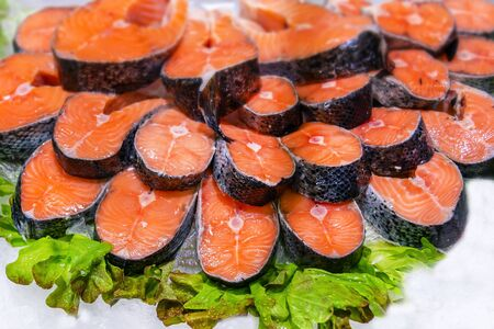 Salmon red fish steak at market. Raw fresh salmon steak as pattern background, close up. Large pile of fish meat with ice texture. Big organic heap of seafood farm salmon fish lined up for sale