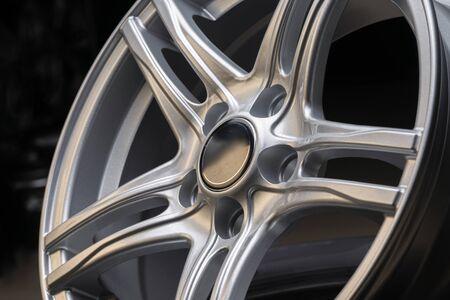 neues silbernes Aluminiumfelgenrad auf schwarzem Hintergrund. schönes Konzept, Nahaufnahme. in einem Reifengeschäft erschossen