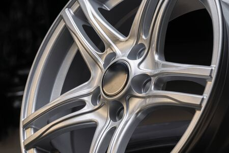 new silver aluminum rim wheel on black background. beautiful concept, close-up. shot in a tire shop