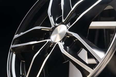 new expensive cast aluminum disc wheel black color, photographed on the tire. dark background, close-up. beautiful bending wheel spokes Stock Photo