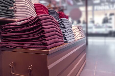 clothes are stacked neatly on a wooden display case in the store. pullovers, sweaters and warm sweaters of different colors are plain. crimson and other shades of warm tones, close-up