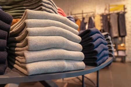 a stack of clothes in the store, pullovers and sweatshirts nicely and neatly stacked in bundles on the table, beige and gray