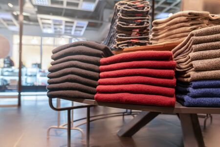 clothes are neatly stacked on the shelves in the store. pullovers, sweaters warm of different colors are plain. red and other warm shades. close up Фото со стока