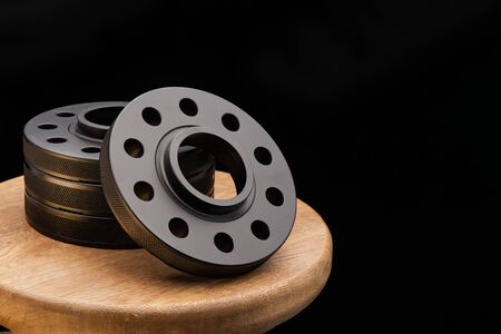 Automotive parts - close up new stainless black metal remote adapter spacer wheel hub of the car. on black background