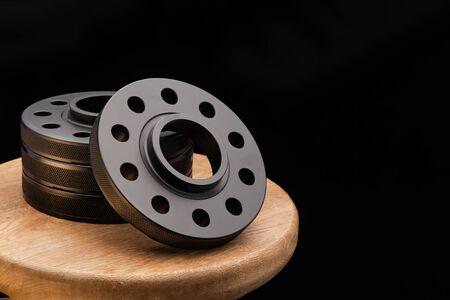 Pièces automobiles - fermer le nouveau moyeu de roue d'entretoise d'adaptateur à distance en métal noir inoxydable de la voiture. sur fond noir Banque d'images