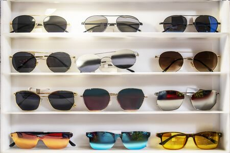Sunglasses of different colors on the store white counter. beautiful and bright, selection and assortment.