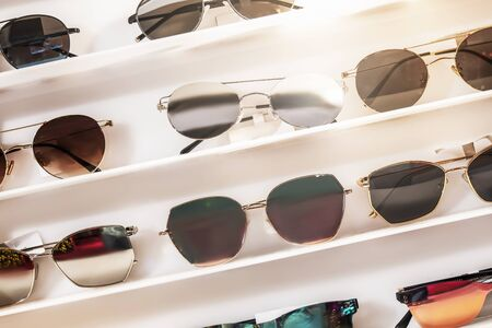 Sunglasses of different colors on the white store counter. beautiful and bright, selection and assortment, tilt fragment, interesting concept