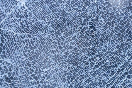 broken glass background. a glass window cracked with cobwebs. abstraction.