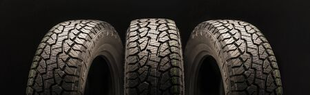 mud all terrain tires for SUVs on a black background close-up, three wheels on a long layout look in different directions. large powerful protector.