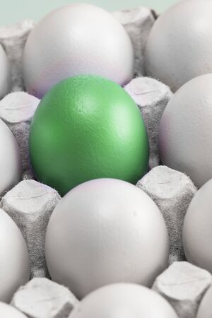 one green egg among many white eggs in the box, close-up. upstart and leader, vertical photo. symbol of individuality. concept for Easter 版權商用圖片
