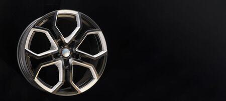 aluminum alloy wheel. Premium cast, the design of the spokes and the wheel rim, a white and black elements on dark background close-up. long layout, copyspace Stock Photo