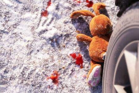 childrens accident on a winter road, Bunny rabbit toy. Death on the road, carelessness and danger. Attention and caution. roadkill winter, blood on snow. Concept, copy space