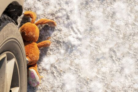 childrens accident on a winter road, Bunny rabbit toy. Death on the road, carelessness and danger. Attention and caution. roadkill winter, Concept, copyspace