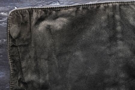 black structural background - old shabby stylish suede, reverse side, old fabric, textile. piece of leather bag, back side on dark, Visible edges with a seam