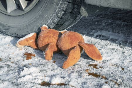 childrens accident on a winter road, Bunny rabbit toy. Death on the road, carelessness and danger. Attention and caution. roadkill winter, blood on snow. Concept Stock Photo