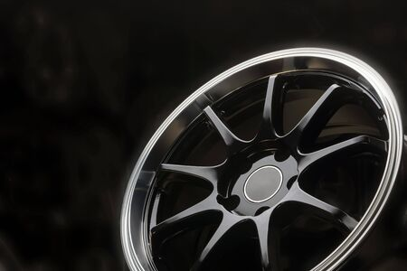 black new alloy wheels with a polished rim on a dark background close up. Stockfoto